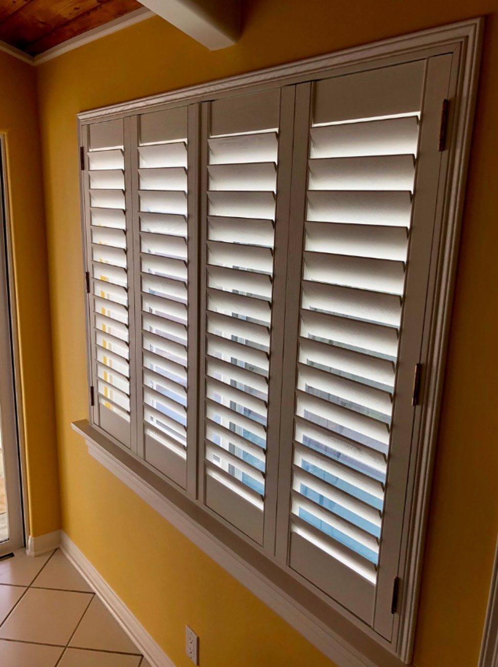 yellow-wall-with-plantation-shutters.png