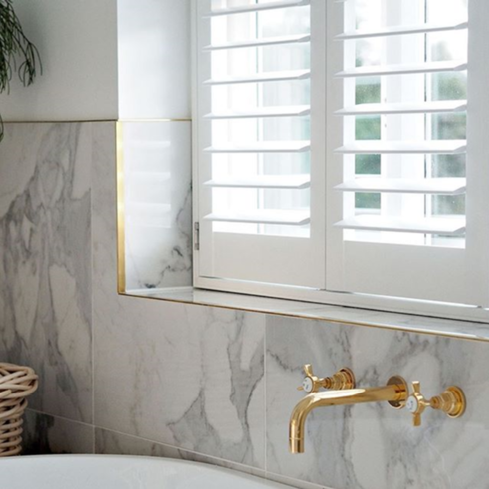 marble-washroom-with-white-interior-shutters.png