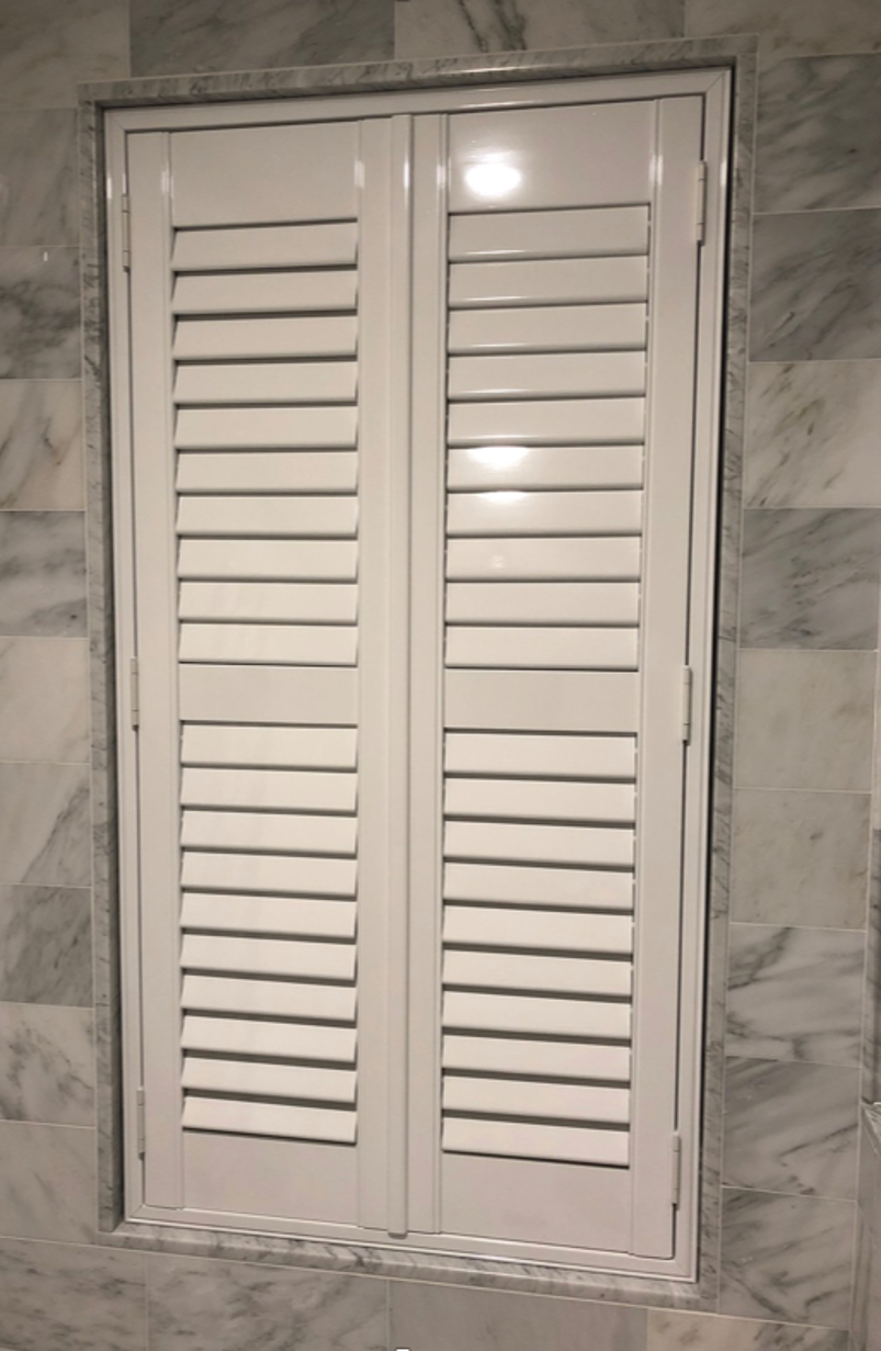 neutral-full-height-shutters-in-a-tiled-bathroom.png