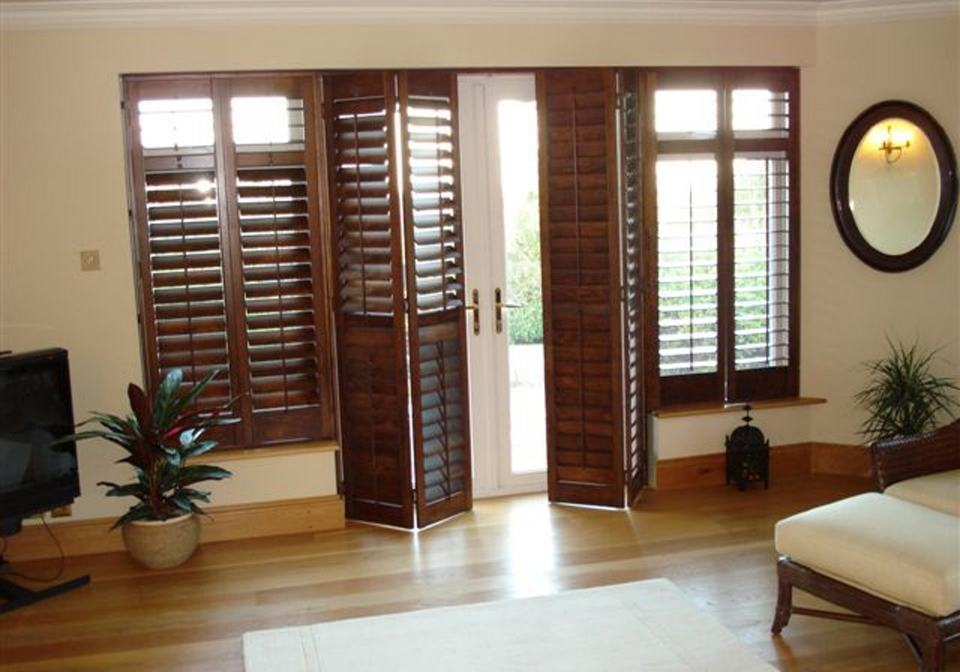 Dark Stained Shutters With Large Slats Covering An External Door.