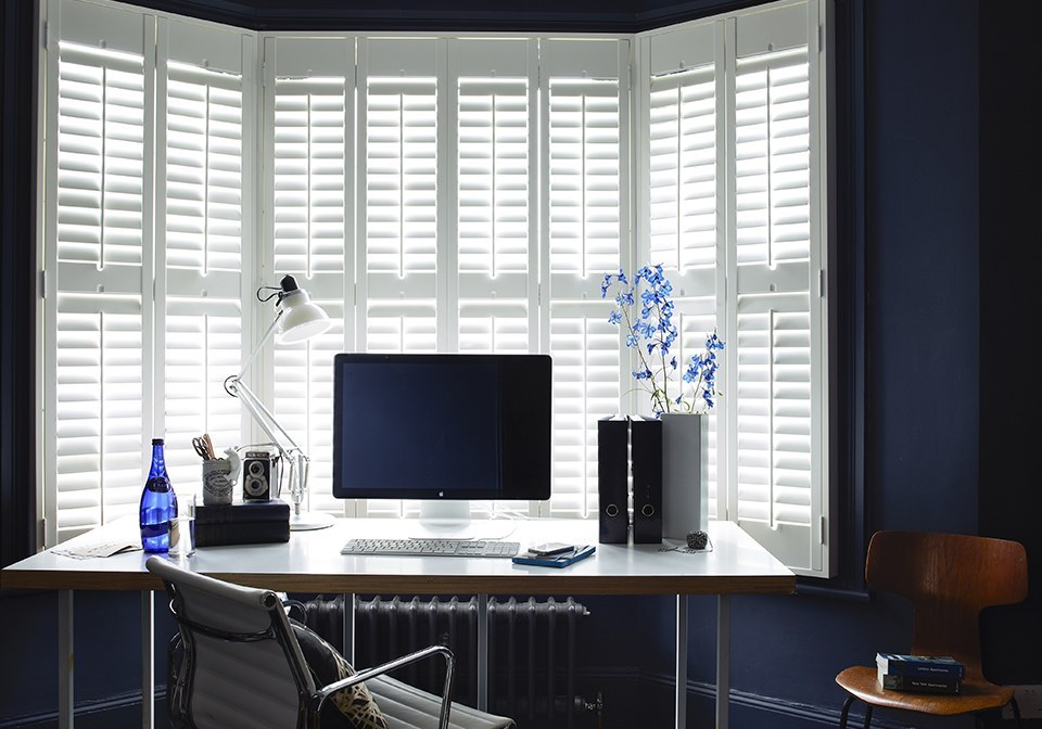"Bright White finished shutters with 2 1/2"" slats in a bay window."