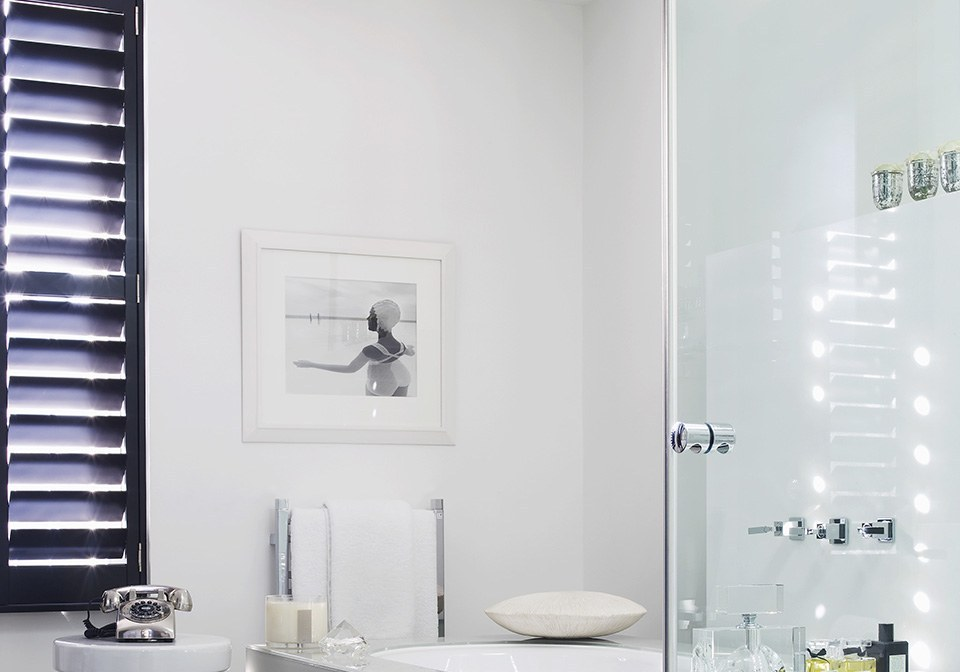 Black designer shutters in contrast to white bathroom